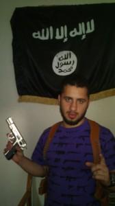Ahmed Samsam med pistol og islamistisk flag. Flaget bruges primært af al-Qaeda og Jabhat al-Nusra.