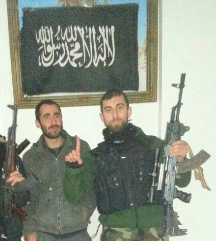 Özgür Deveci som jihadist med al-Qaeda flag i baggrunden, Syrien/Tyrkiet (2013).