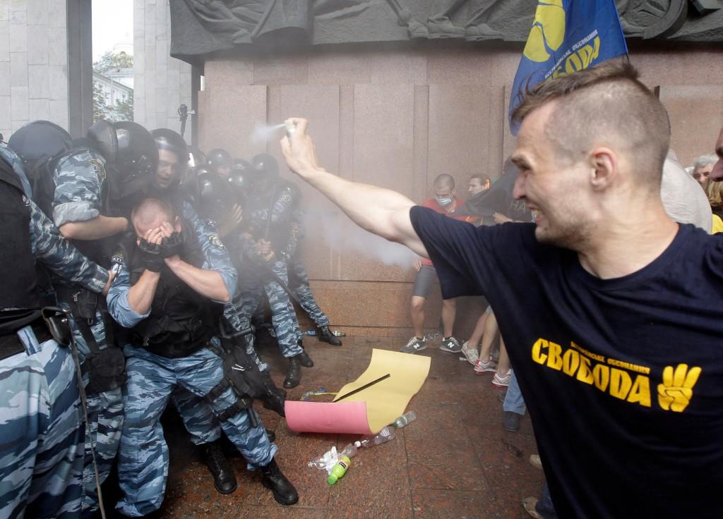 En mand med en t-shirt fra den fascistiske bevægelse Svoboda overfalder betjente med peberspray.